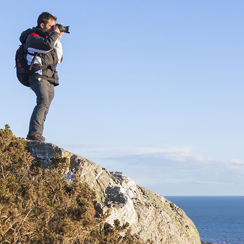 Photogragpher backpacker taking pictures at the cliff
